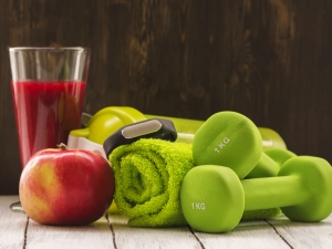 Dumbbells, red smoothie and an apple